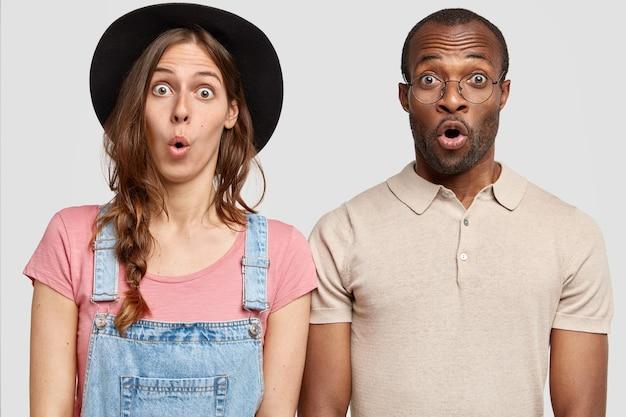 Verbaasde vrouw en man kijken met grote verbazing, verwonderen zich iets, staan dicht tegen witte muur