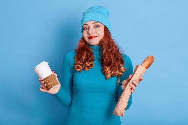 Verbaasde vrouw haalt schouders op, spreidt haar handen met afhaalkoffie en lang stokbrood