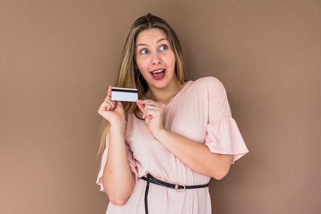 Verbaasde vrouw in kleding die zich met creditcard bevindt