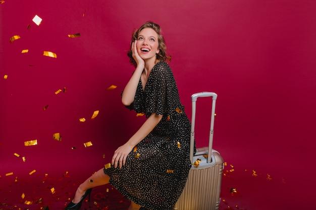 Verbaasde vrouw in lange gestippelde jurk kijken naar sprankelende confetti op welkom thuisfeestje