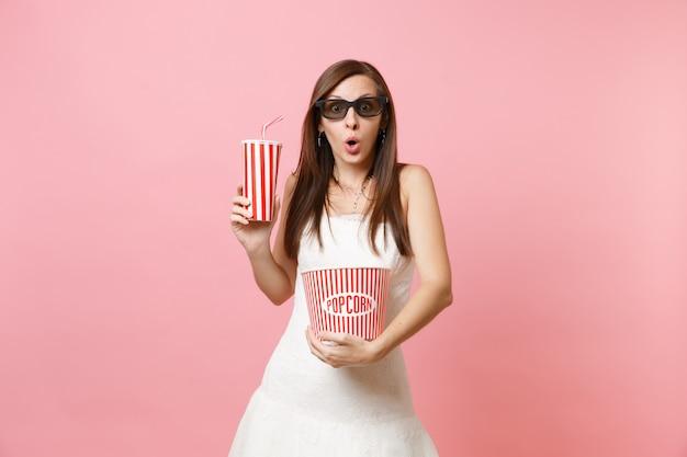 Verbaasde vrouw in witte jurk, 3d-bril kijken naar filmfilm, met emmer popcorn, plastic beker frisdrank of cola