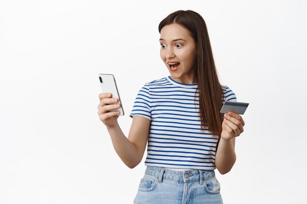Verbaasde vrouw kijkt naar het smartphonescherm, houdt een creditcard vast, koopt een internetwinkel, staat tegen een witte muur