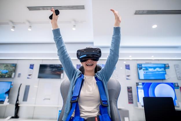Verbaasde vrouw met behulp van een vr-bril en armen omhoog. nieuwe technologieënconcept.