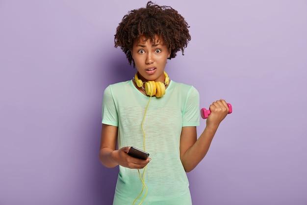Verbaasde vrouw met donkere huid houdt smartphone vast, kiest track voor fitness uit de afspeellijst van mobiele telefoons
