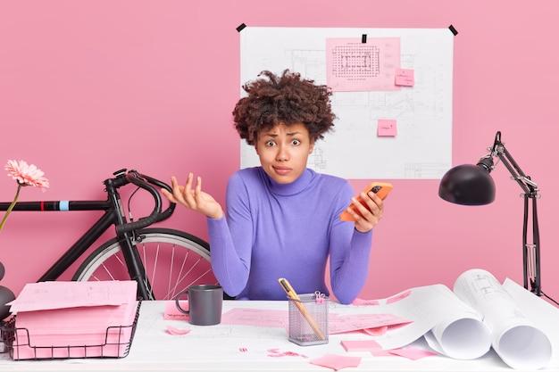 Verbaasde vrouw met donkere huid werkt op desktop houdt mobiele telefoon vast en uit twijfel, heeft sceptische uitdrukking maakt schetsen