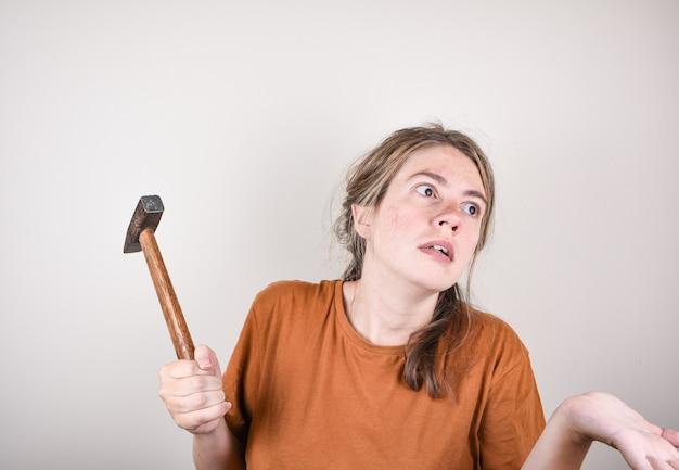 Verbaasde vrouw met een hamer in haar handen, die niet weet hoe ze reparaties in huis moet uitvoeren. vrouw met hamer is verrast door de vraag.