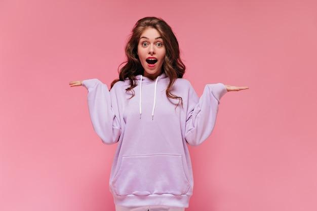Verbaasde vrouw met grijze ogen in paarse hoodie kijkt in de camera