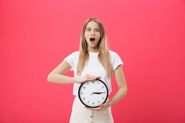 Verbaasde vrouw met klok. de verraste vrouw in witte t-shirt houdt zwarte klok