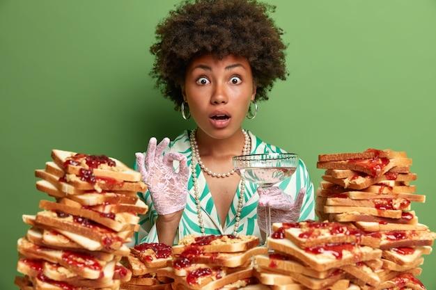 Verbaasde vrouw met krullend haar maakt goed gebaar en staart, geniet van een cocktail, staart met afgeluisterde ogen, hoort verbluffend nieuws, is goed gekleed, staat over groene muur bij toast