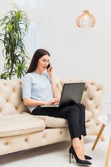 Verbaasde vrouw met laptop op laag die telefonisch spreekt