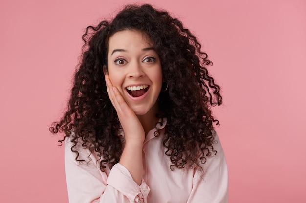 Verbaasde vrouw, mooi meisje met donker krullend haarbroodje. het dragen van oorbellen en een pastelroze shirt. heeft make-up. verrast haar gezicht aanraken