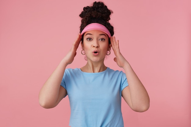 Verbaasde vrouw, mooi meisje met donker krullend haarbroodje. ik draag een roze klep, oorbellen en een blauw t-shirt. heeft make-up. haar hoofd aanraken