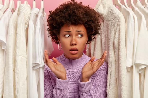 Verbaasde vrouw spreidt haar handpalmen, staat tussen modieuze witte kleren in wadrobe, besluit wat ze aan zal trekken, gefocust opzij met een ontevreden uitdrukking.