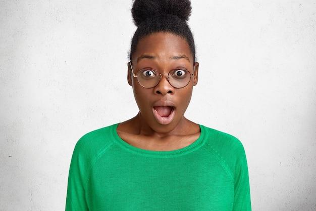 Verbaasde vrouw van middelbare leeftijd met een donkere huid, opent mond van verbazing, krijgt onverwacht nieuws, gekleed in groene felle trui