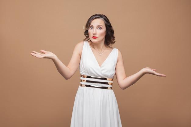 Verbaasde vrouw van middelbare leeftijd zegt dat ik het niet weet. emotionele vrouw in witte jurk, make-up, rode lippen en donker krullend kapsel. studio-opname, binnen, geïsoleerd op beige of lichtbruine achtergrond