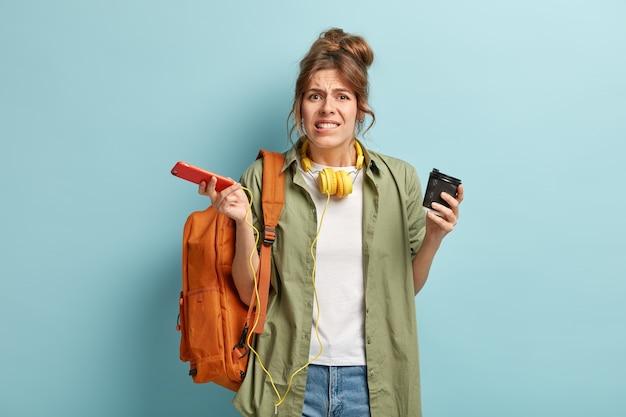 Verbaasde vrouwelijke blogger houdt mobiele telefoon en afhaalkoffie vast, kan geen transactie of betaling uitvoeren