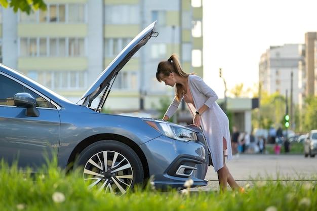 Verbaasde vrouwelijke chauffeur die in een stadsstraat in de buurt van haar auto staat met een opgeklapte motorkap die naar een kapotte motor kijkt.