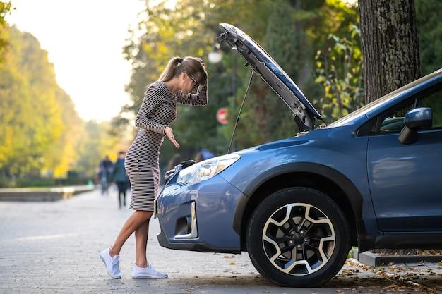 Verbaasde vrouwelijke chauffeur staat op een straat in de buurt van haar auto met opgedoken motorkap en kijkt naar kapotte motor.