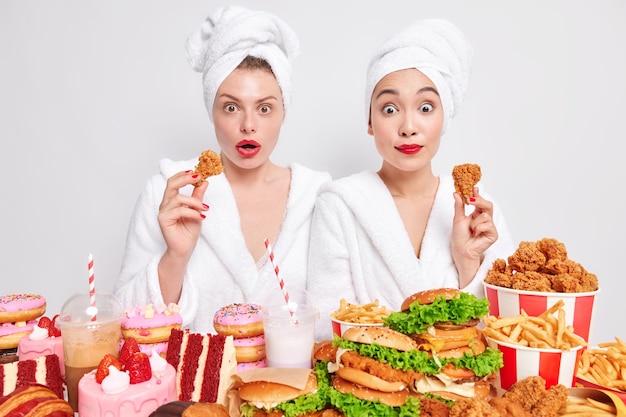 Verbaasde vrouwelijke modellen eten gefrituurde kipnuggets hebben ongezonde voeding, geven niet om voeding