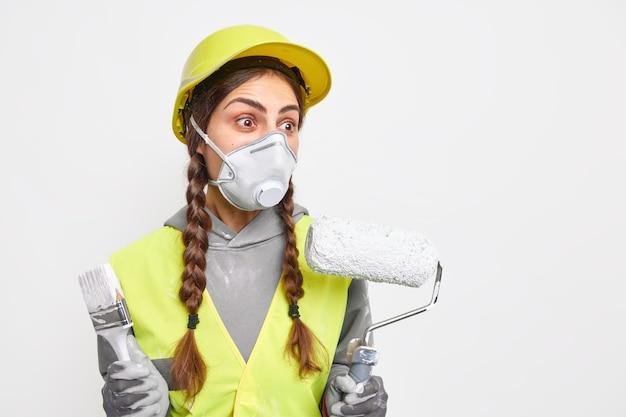 Verbaasde vrouwelijke reparateur of decorateur houdt schildergereedschap vast om te schilderen