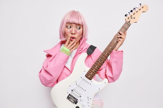 Verbaasde vrouwelijke soliste kijkt verbijsterd naar elektrische akoestische gitaar speelt muziek als beroemde rockster die muzikale uitvoering gaat opnemen draagt roze jashandschoenen