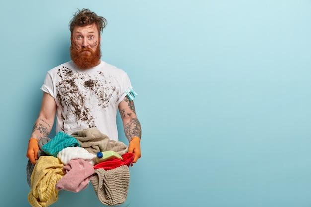 Verbaasde, vuile huishoudster draagt een casual wit t-shirt, houdt een mand met linnen vast, doet de was tijdens het weekend