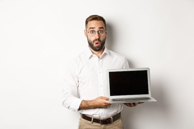Verbaasde zakenman die het laptopscherm toont, die zich tegen witte achtergrond bevindt.