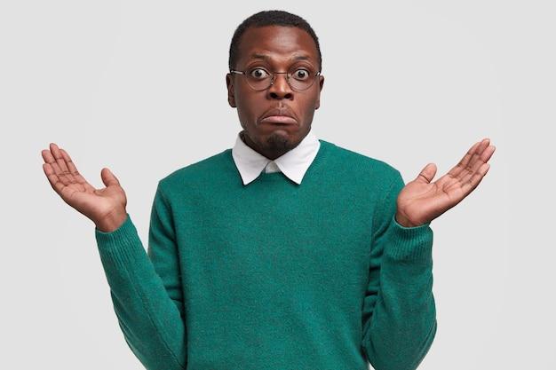 Verbaasde zwarte man heeft geen idee en vragende blik, spreidt zijn handen, probeert iets te begrijpen of een oplossing te vinden, poseert in een onbewust gebaar