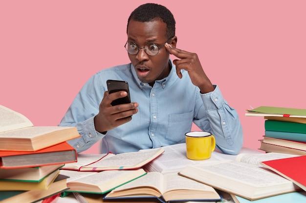 Verbaasde zwarte man staart naar mobiele telefoon, leest nieuws op internetwebsite, draagt formele kleding, bereidt zich alleen voor op seminar
