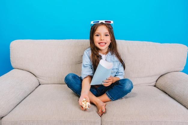 Verbazend gelukkig klein meisje met lang donkerbruin haar dat naar camera op bank glimlacht die op blauwe achtergrond wordt geïsoleerd. 3d-bril op het hoofd dragen, zich voorbereiden op het kijken naar film met popcorn, positiviteit uitdrukken