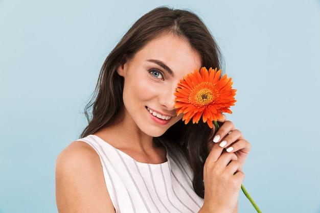 Verbazend mooie jonge vrouw geïsoleerde muur met bloem.