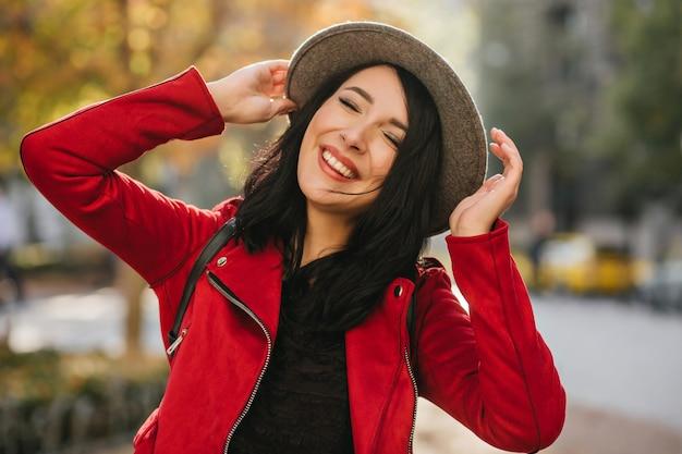 Verbazende witte vrouw die met gesloten ogen op aardmuur lacht