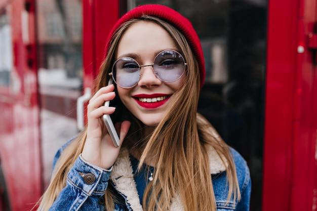 Verbazende witte vrouw in spijkerjasje poseren met telefoon op rood