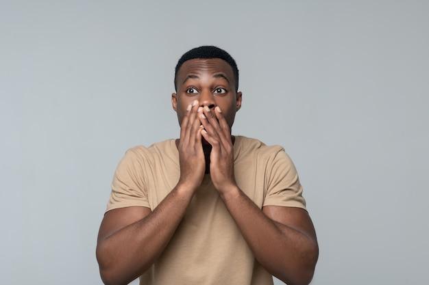 Verbazing. aantrekkelijke jonge verbaasd donkere gevilde man in lichte t-shirt aanraken van de mond met handen staan in studiofoto