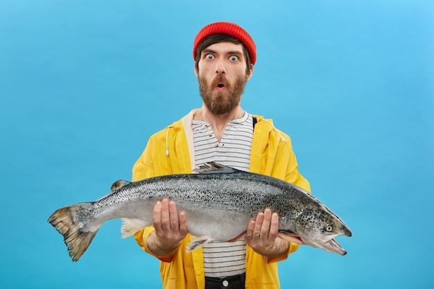 Verbazing en onverwachts concept. geschokte jonge visser met dikke baard kijkt met afgeluisterde ogen en open mond terwijl hij een enorme vis vasthoudt, niet te geloven dat hij hem alleen kan vangen