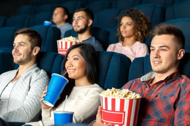 Verbazing in de bioscoop. close-upschot van drie vrienden die samen van kijkend films bij de bioscoop genieten
