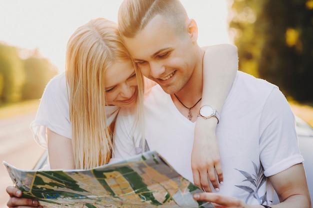 Verbazingwekkend jong kaukasisch stel dat op de rug van de zorg rust terwijl ze nieuwe plaatsen op de kaart zoeken om te verkennen tijdens het reizen, waar het meisje een hand om de nek van zijn vriendje legt.