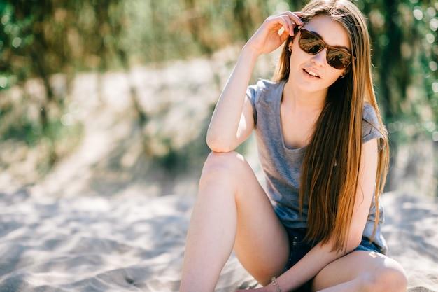 Verbazingwekkend jong meisje dat op strand siiting en camera bekijkt. mode portret van mooie vrouw spelen met zand beayond zee. vrij vrolijk persoon lachend gezicht. reiziger ontspannen in de natuur buiten.