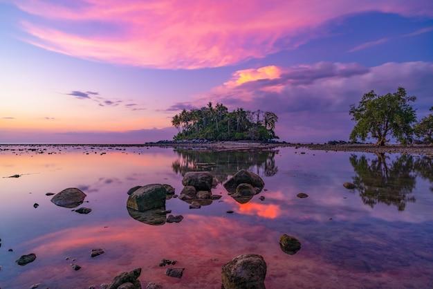 Verbazingwekkend licht sunset hemel over klein eiland in tropische zee zonsondergang of zonsopgang tijd bij eb dag met rotsen op de voorgrond prachtige natuur landschap zeegezicht.