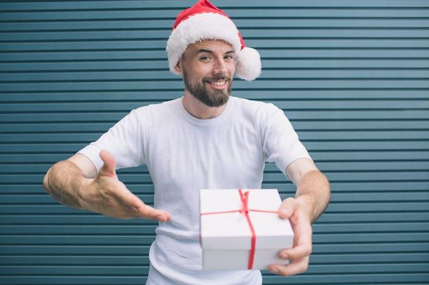 Verbazingwekkende en aardige persoon staat en kijkt op camera. hij houdt een witte doos vast en wijst erop met de hand. bebaarde man is blij aanwezig te hebben. geïsoleerd op gestreept