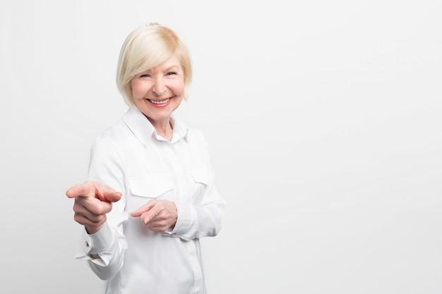 Verbazingwekkende en vrouwelijke oude vrouw draagt een witte blouse en wijst op iets. ze ziet er zelfverzekerd en gelukkig uit.