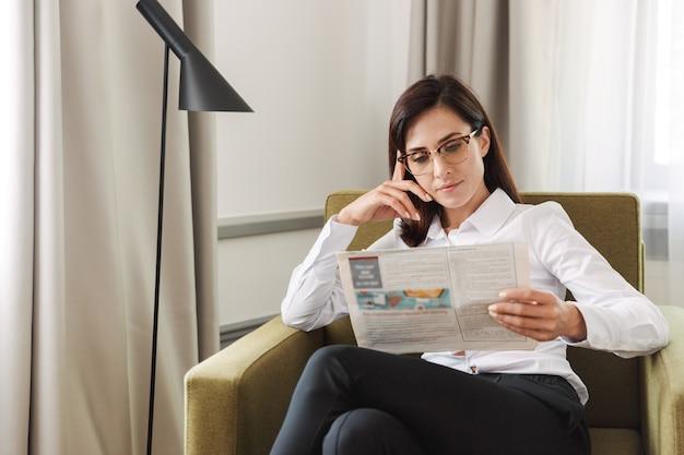 Verbazingwekkende geconcentreerde mooie jonge zakenvrouw in formele kleding binnenshuis thuis krant lezen.