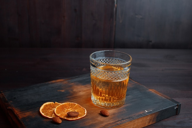 Verbazingwekkende gouden scotch whisky in een kristalglas versierd met zoete stukjes sinaasappel en pinda's, staat op een oude houten tafel in een pub. heerlijk mannelijk drankje. weekend aan de bar