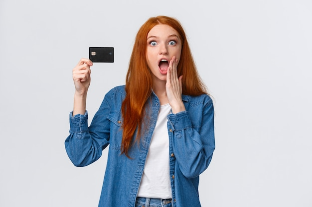 Verbazingwekkende kortingen, bankdienstconcept. taille-portret verrast en verbaasd knappe roodharige vrouw met creditkaart, reageer geamuseerd op prachtige kans, weggevertje