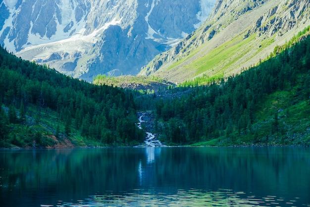 Verbazingwekkende kreek van gletsjer stroomt in meer. schaduw van bergen op bos.