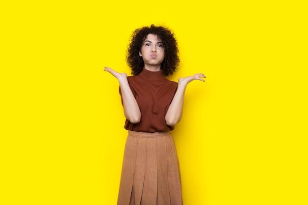 Verbazingwekkende krullende harige vrouw gebaart met haar lippen en handen poseren in een jurk op een gele studiomuur