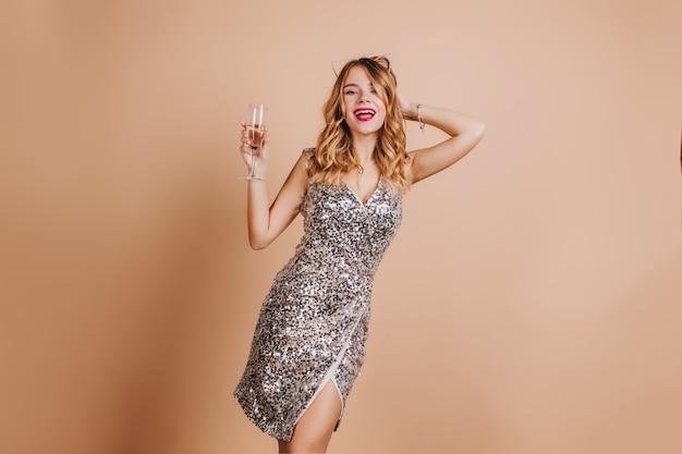 Verbazingwekkende krullende jonge vrouw genieten van kerstfeest en poseren in trendy sparkle jurk
