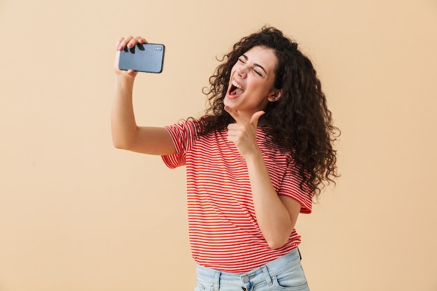 Verbazingwekkende krullende jongedame maken selfie praten door mobiele telefoon te wijzen.