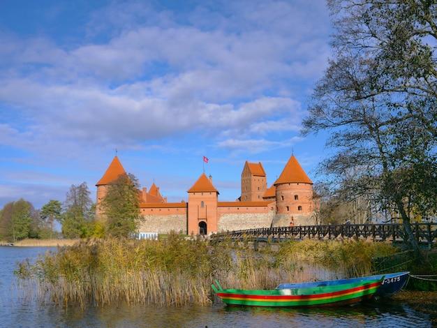 Verbazingwekkende landschapsmening van trakai kasteel kleurrijke boot en houten brug vóór de poorten, litouwen.