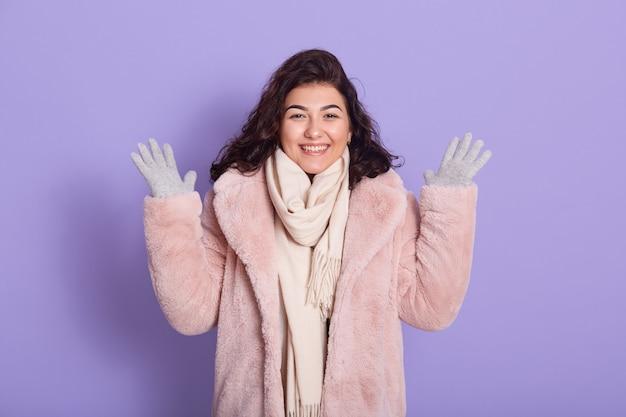 Verbazingwekkende mooie dame opgeheven handen in verrukking, draagt bontjas, sjaal en wanten, ziet er gelukkig uit, heeft goed nieuws, verheugt zich, glimlacht tandachtig, toont witte tanden, geïsoleerd op een lila achtergrond.